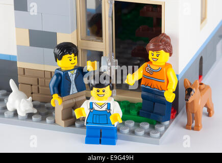 Tambov, Russian Federation - January 08, 2014 Happy LEGO family standing near his home with pets. - Stock Photo