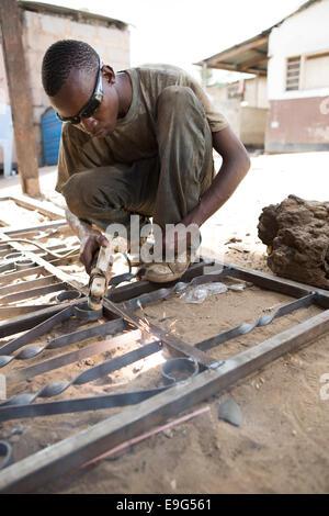 Welder at a workshop in Dar es Salaam, Tanzania, East Africa. - Stock Photo