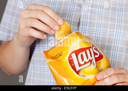 Tambov, Russian Federation - January 20, 2013 Hand takes out potato chip from Lay's bag. It is a potato chips with - Stock Photo