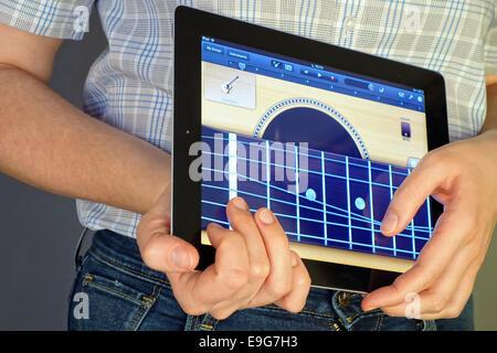 Tambov, Russian Federation - January 20, 2013 Woman's hand playing guitar with GarageBand App on an Apple iPad. - Stock Photo