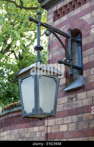 Metal lantern on a brick wall with glass - Stock Photo
