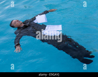 Senior man floating among papers in water - Stock Photo