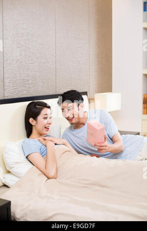 Surprised woman receiving gift from man - Stock Photo