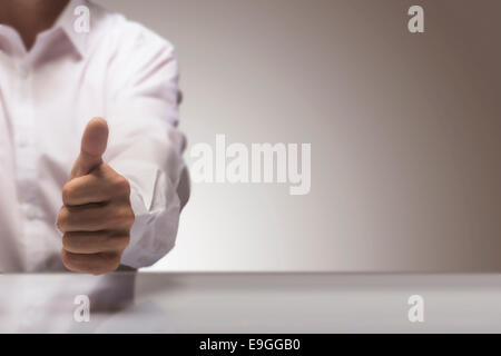 Man with one thumb up at the background of a glossy table and copy space on the right, concept image for illustration - Stock Photo