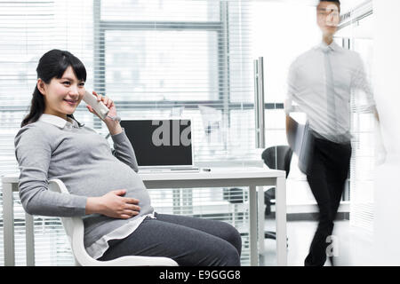 Pregnant businesswoman on the phone and businessman walking out - Stock Photo