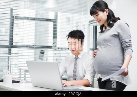 Pregnant businesswoman working with colleague - Stock Photo