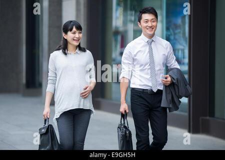Pregnant businesswoman walking with businessman - Stock Photo