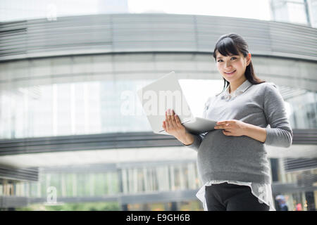 Pregnant businesswoman holding laptop - Stock Photo
