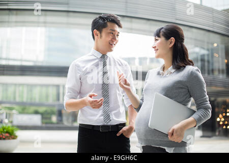 Pregnant businesswoman talking with colleague - Stock Photo