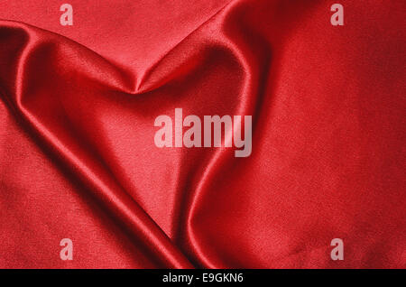 Closeup of red satin draped in the form of heart - Stock Photo