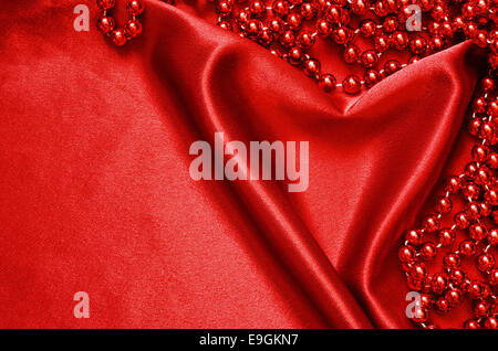 Red satin draped in the form of heart and beads - Stock Photo