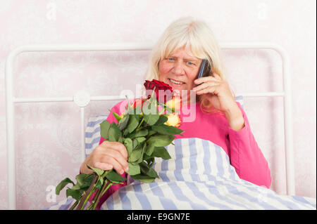 Happy woman in pink pajama sitting in bed with roses and talking on the phone - Stock Photo