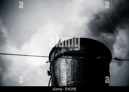 Closeup view of the steam train chimney. Black smoke comes out of a chimney. Black and white photography - Stock Photo