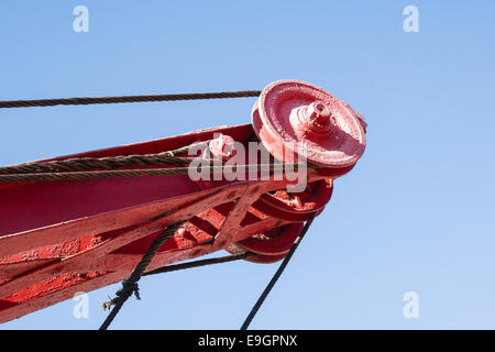 Closeup view of a railway crane boom or arm and ropes against the background of clear blue sky - Stock Photo