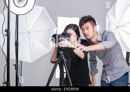 Two photographers taking picture in studio - Stock Photo