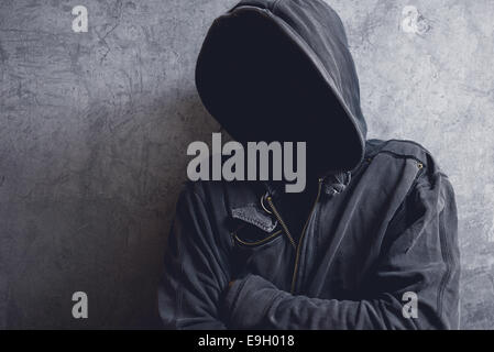 Faceless unknown and unrecognizable man with hood in dark room, spooky criminal person. - Stock Photo