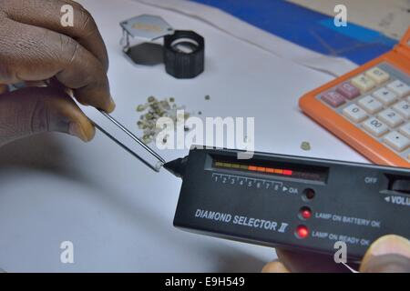 Diamond dealer inspecting a diamond for its authenticity, Koidu, Koidu-Sefadu, Kono District, Eastern Province, - Stock Photo