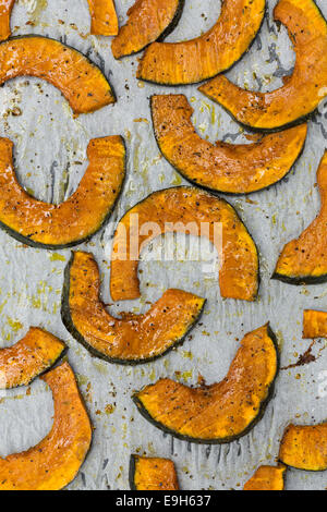 Roasted slices of pumpkin on a baking tray - Stock Photo