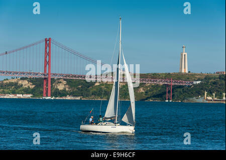Sailing boat on the Tagus River in front of the Ponte 25 de Abril suspension bridge, Belém, Lisbon, Lisbon District, - Stock Photo