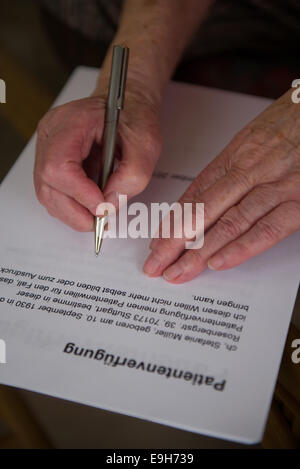 Hands of a 82-year-old woman signing a living will, Germany - Stock Photo
