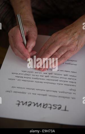 Hands of a 82-year-old woman signing a will, Germany - Stock Photo