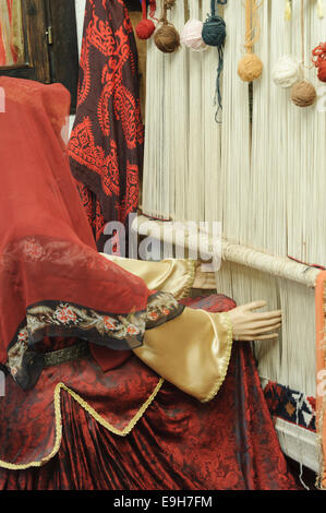 Carpet weaver model in traditional national costume with old wooden loom - Stock Photo