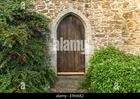 An old arched heavy wooden door set in an ancient stone wall - Stock Photo