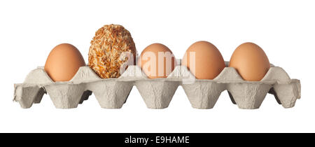 Preserved egg in the midst of a row of chicken eggs isolated on white background - Stock Photo