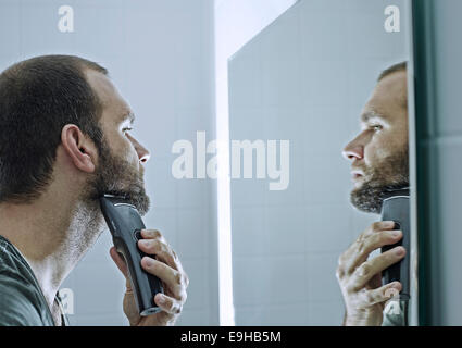 Man shaving his beard in front of a mirror - Stock Photo
