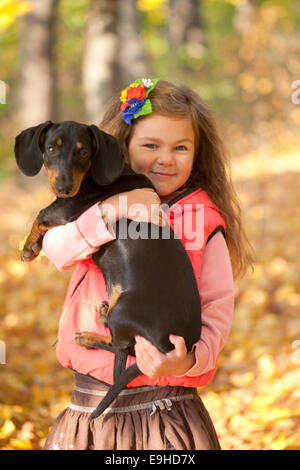 Little kid with a dachshund puppy. Girl and dog cuddling - Stock Photo