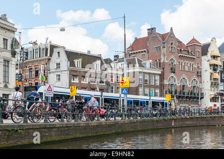 Bicycles locked to the railings along a canal in the city of Amsterdam, Netherlands Stock Photo