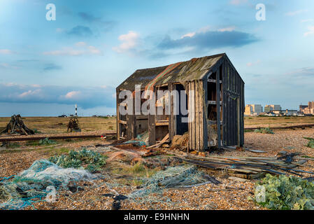 An abandoned fisherman's hut fallen into ruin and disrepair on Dungeness beach in Kent - Stock Photo