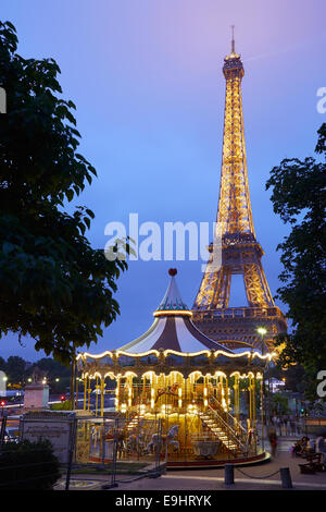 Eiffel tower in Paris and carousel in the evening - Stock Photo