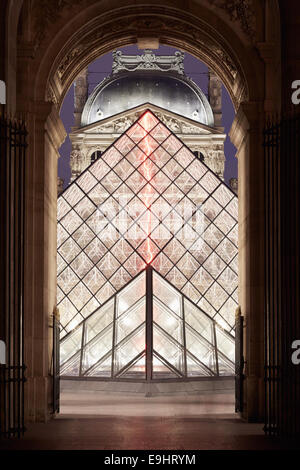 Louvre pyramids and museum through arch view at night in Paris, France - Stock Photo