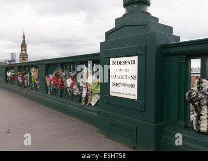Samaritans sign with emergency phone number on the Tyne Bridge with floral tributes, north east England - Stock Photo