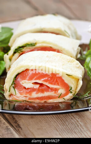 Salmon lavash rolls with cheese and herbs on glass plate, close up view - Stock Photo