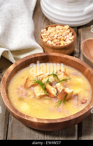 Pea soup with bacon and croutons in wooden bowl on rustic table - Stock Photo