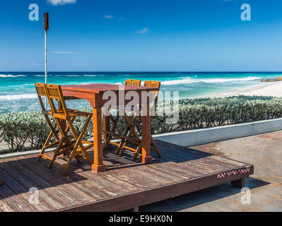 Restaurant table and chairs at a beach front location in Barbados. - Stock Photo