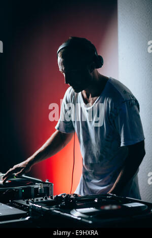 Silhouette of dj at work in night club. Shallow depth of field - Stock Photo