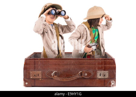 Children's couple in safari clothes playing inside a suitcase - Stock Photo
