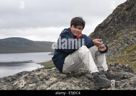 Teenage boy having a rest by Bessvatnet lake during a hike along Besseggen mountain in Jotunheimen national park, - Stock Photo
