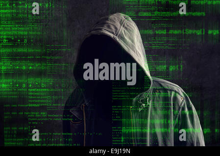 Faceless hooded anonymous computer hacker with programming code from monitor - Stock Photo