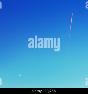 Airplane trail of fuel and moon on blue sky. - Stock Photo