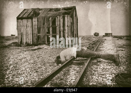 Surreal vintage photo of woman lying on a railway track next to a happy sign - Stock Photo