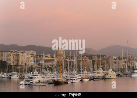 Boats and holiday apartments on the coast at Palma de Mallorca in Palma, Spain, at sunrise sunset. - Stock Photo