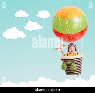 cute kid on hot air balloon in the blue sky - Stock Photo