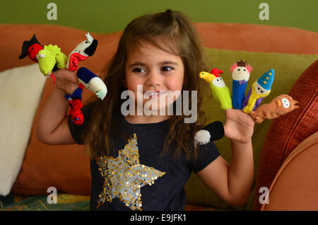 Child (girl age 04) play with finger dolls at home. - Stock Photo
