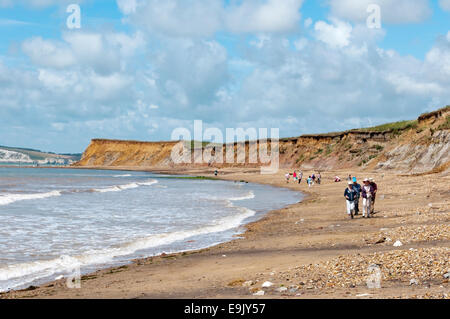 Holidaymakers walking along the beach at Brook Bay on the south coast of the Isle of Wight. - Stock Photo