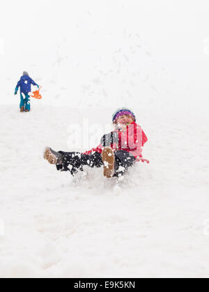 small girl sledging fast down a steep hill in a cloud of snow with small boy walking up hill in background - Stock Photo