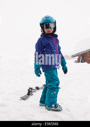 small boy in ski clothes, helmet and goggles, ready to go skiing with falling snow. - Stock Photo